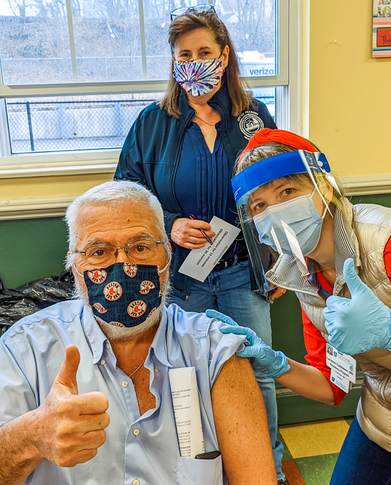 Glen Jalbert, Fairweather resident, and Caroline Cubbison, resident physician at North Shore Medical, give a thumbs up after Glen is vaccinated. Sharon Cameron, Director of the Peabody Health Department, looks on.